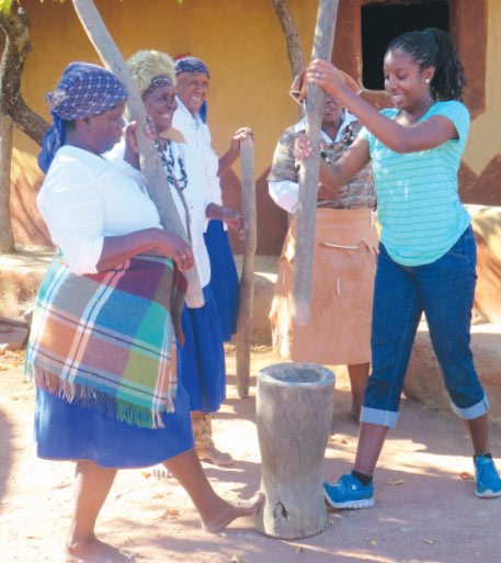 A UCF student helps women pound grain during an exchange program in Botswana.