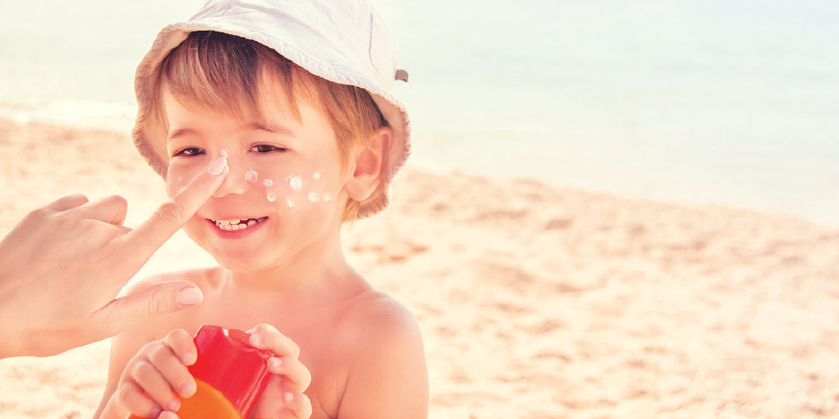 Hand placing sunscreen on a small boy at the beach