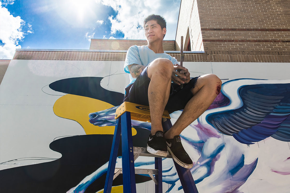 Boy Kong sits on the top step of a ladder holding a paint brush. In the background is the Pegasus mural at UCF in progress. The light from the sun glares in the top of the frame with a bright blue sky with white clouds.