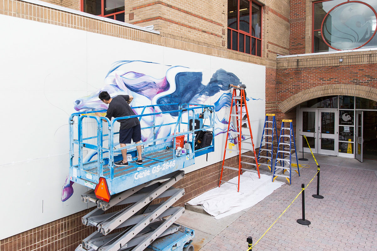 Standing on a blue lift, Boy Kong paints details on the face of Pegasus that is still a work in progress while his brother Chris Troung stands on an orange ladder and fills in the black background that will be a wing. Part of the entrance to the Student Union is in view.