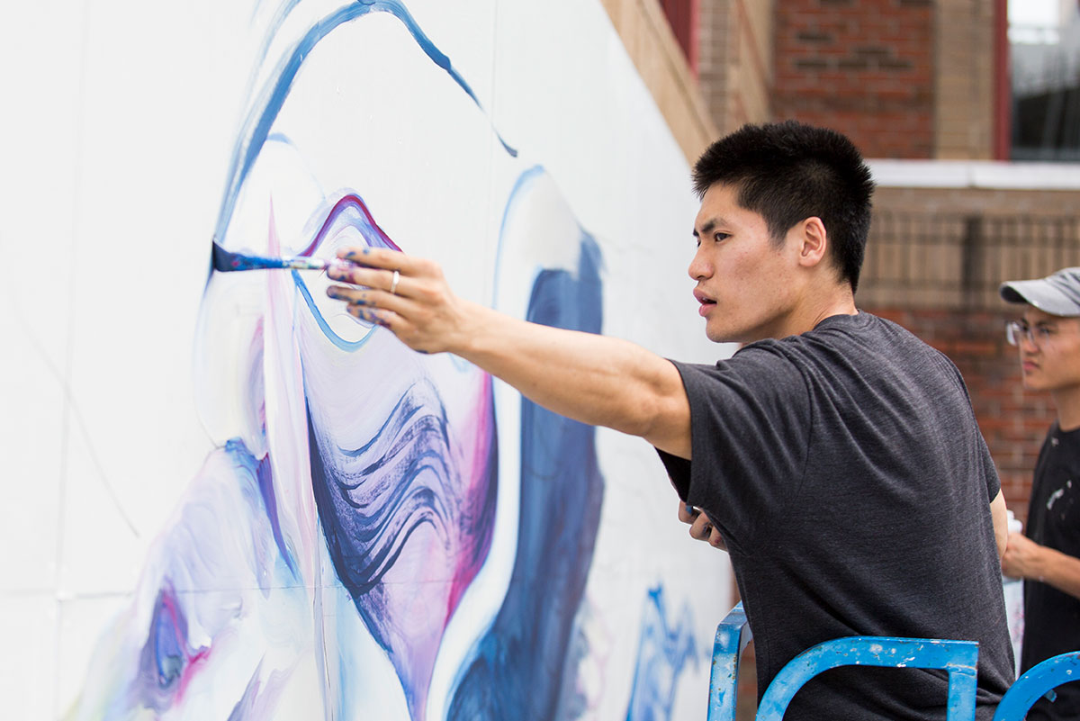 Boy Kong paints the outline of a wing on a large white background on a wall.