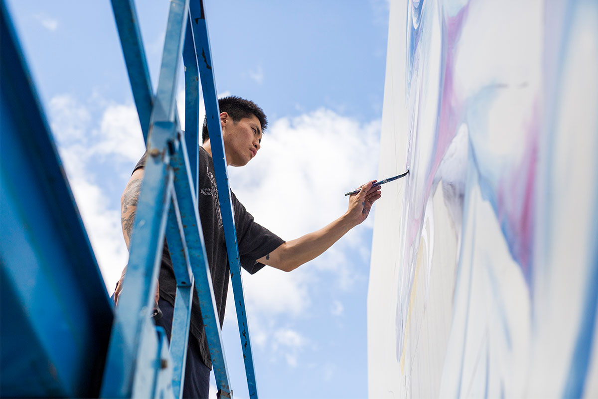 Shown at angle looking up from the ground, Boy Kong stands in a blue lift painting details on the mural.