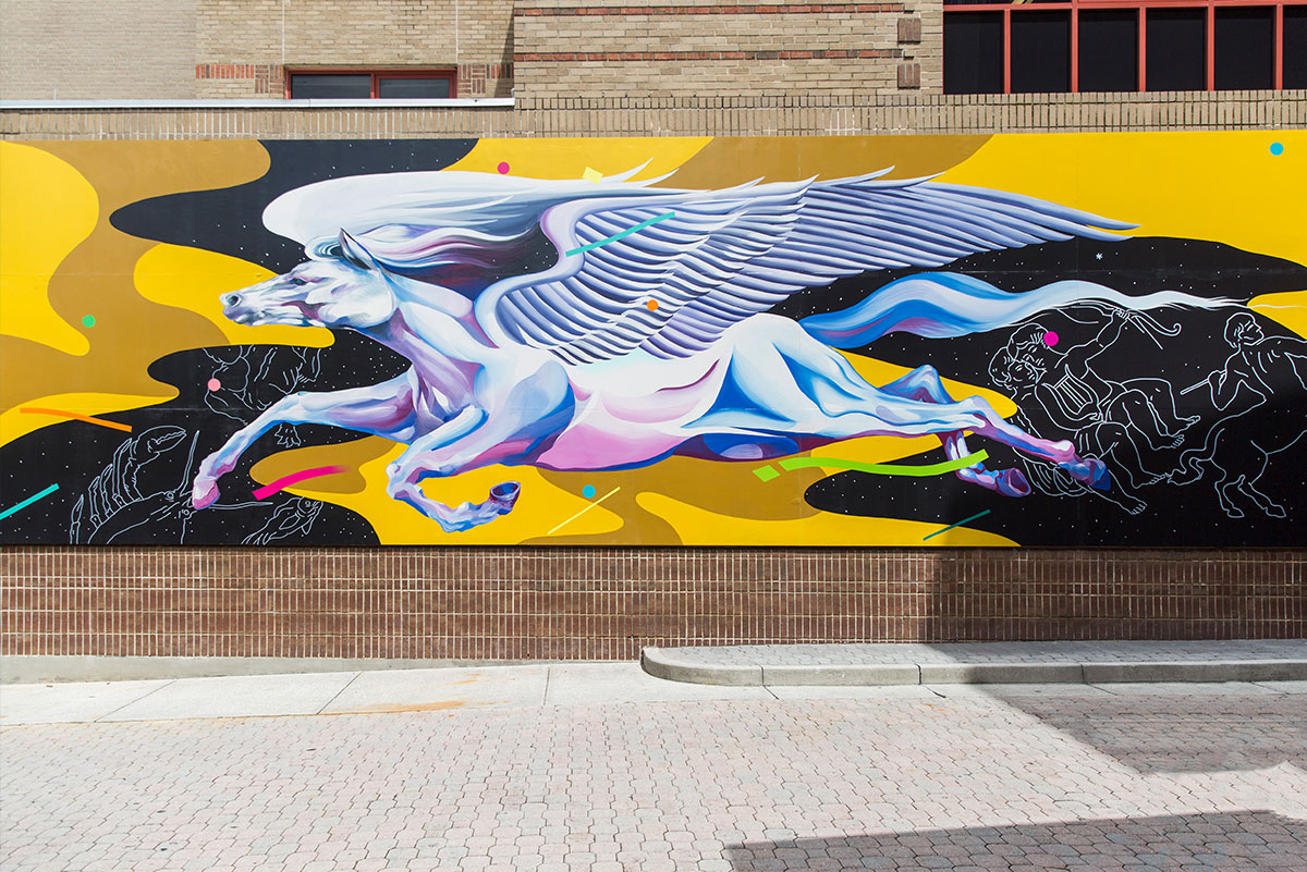 The completed Pegasus mural at UCF on the wall of the Student Union shows a white horse with giant wings, with shading done in pinks, purples, and blues, in flight on a yellow and black swirly background. In the black sections, you can see outlines of constellations. Neon colored dots and dashes in pinks, greens, and blues look like confetti.