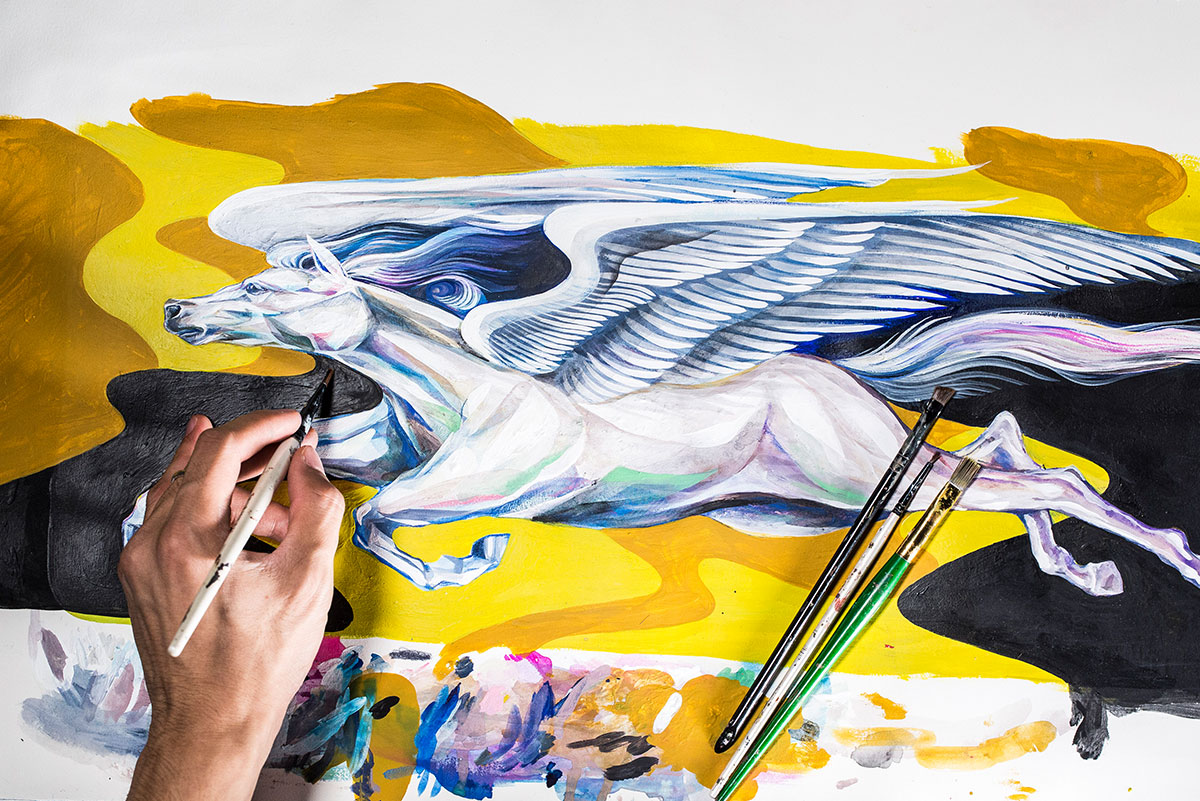 An image of the painting from above shows Boy Kong's hand painting a white, winged horse in flight with a yellow and black background. Paint brushes lay on top of the painting.
