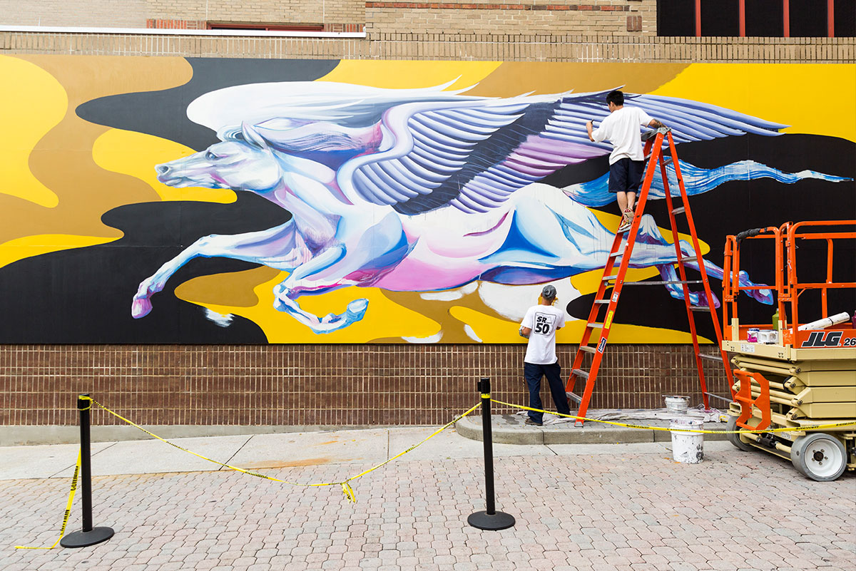 A wide shot of the mural at UCF shows a mostly completed horse with giant wings in flight on a black and yellow background. Boy Kong stands on top of an orange ladder in front of the mural, while Chris Troung holds it.