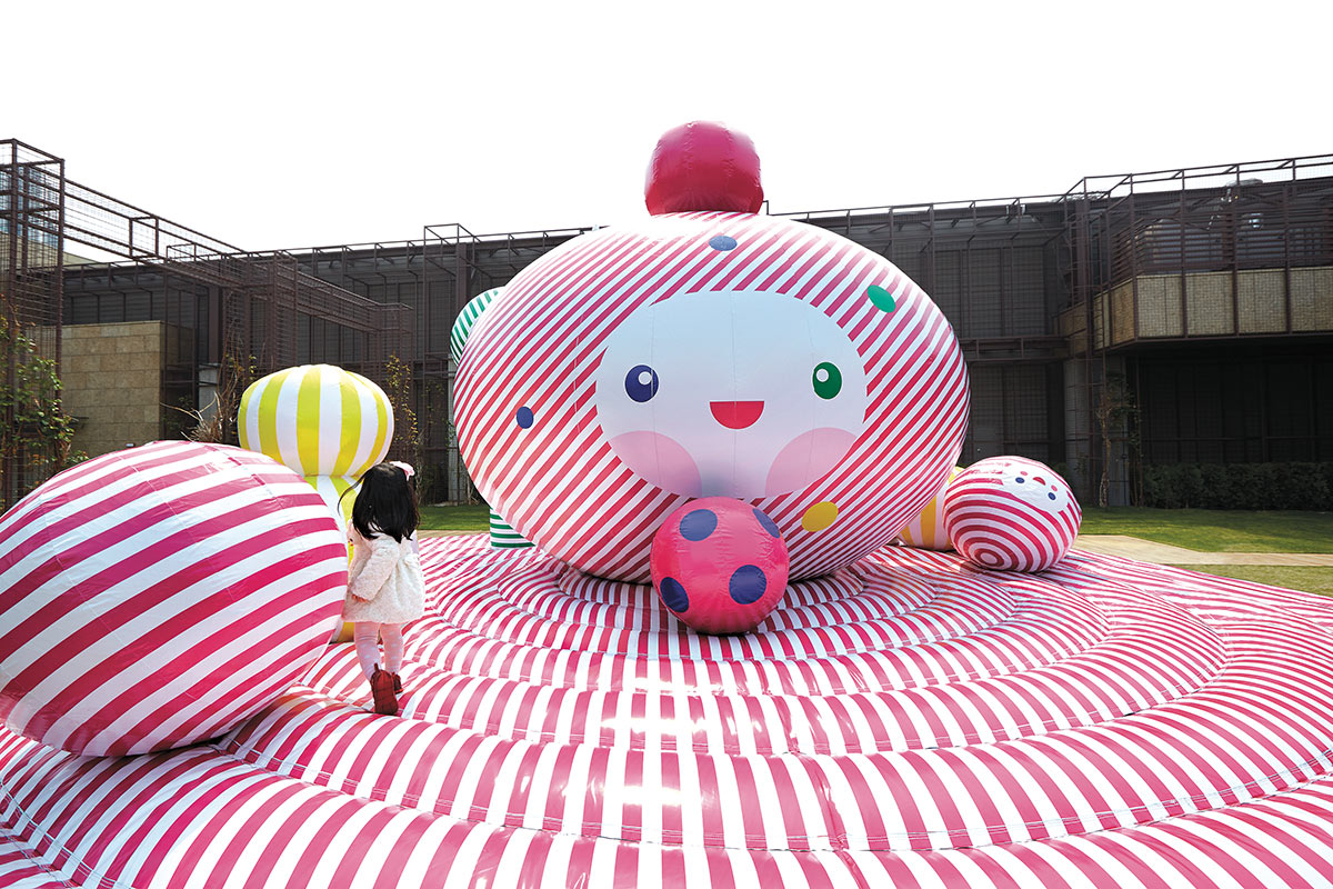 "<em>Happy Gift</em>, which was commissioned in 2013 by the Hyundai Family of Korea to be publicly exhibited at Hyundai Department Gardens in Seoul, is a ""hypnotically striped,"" 25-foot-wide inflatable bounce house designed for both children and adults."