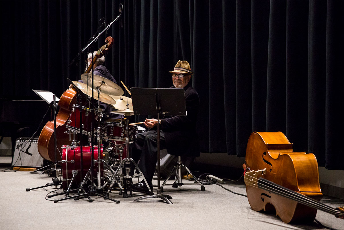 UCF Instructor Marty Morell plays the drums. He is looking a music stand. An upright base lies on its side to the right of him.