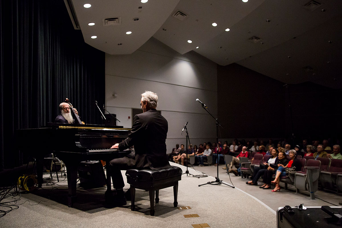 The man is seen playing the piano. His back is to the photographer. Facing him is a man playing an upright bass. The audience can be seen to the right.