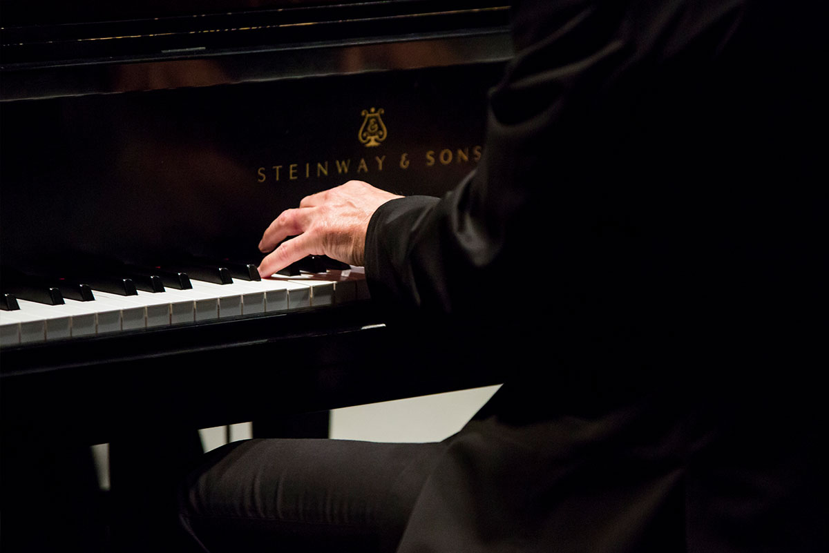 Hands are seen playing the keys of a Steinway piano.