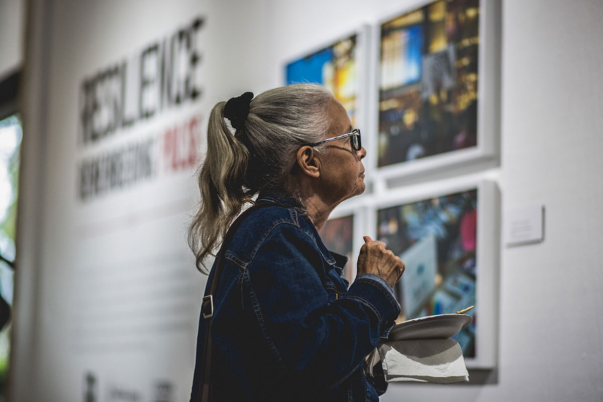 An older hispanic-looking woman looks at artwork in a gallery.