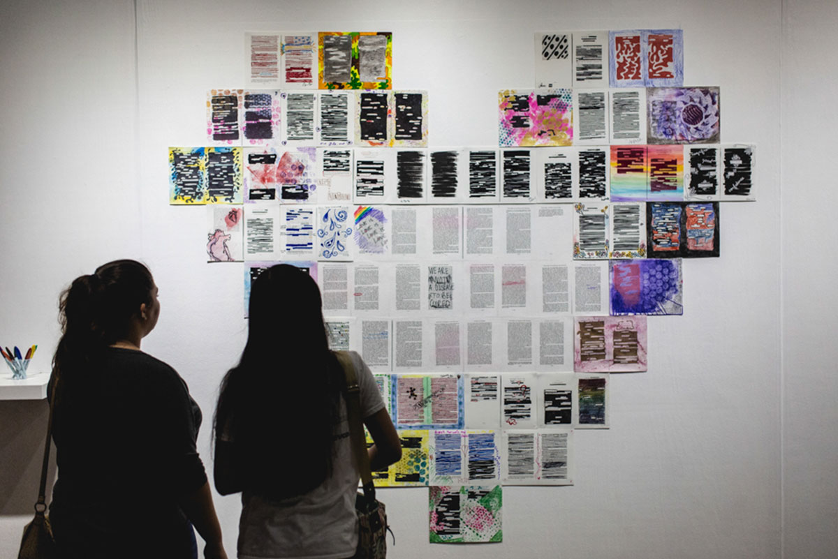 The silhouettes of two women are seen looking at a giant installation of pieces of paper torn from a book, colored, and shaped into a giant heart.