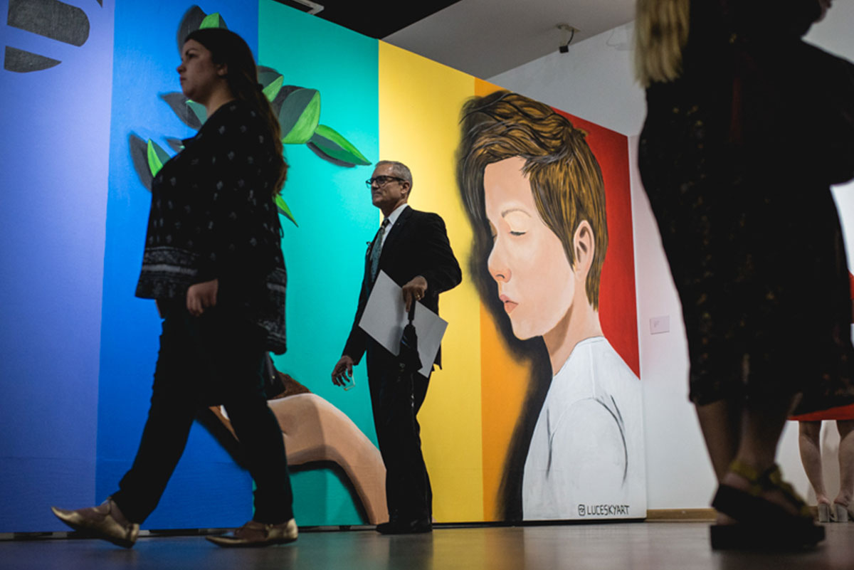 People are seen walking in front of a large mural of an androgynous looking person with short brown hair wearing a white shirt on a rainbow-colored background.