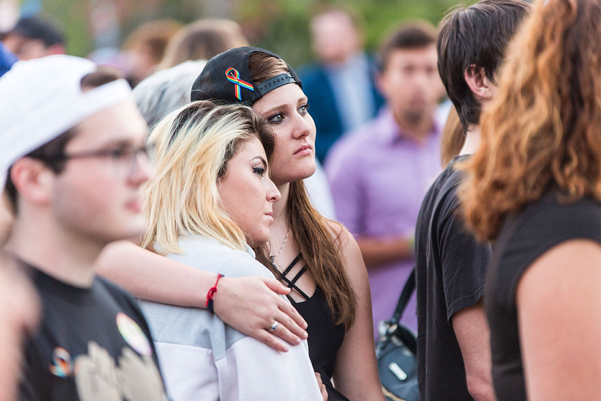 One woman in a black baseball hat turned backward with rainbow ribbon has her arm wrapped around another woman, who rests her head on the shoulder of the woman wearing the black hat.