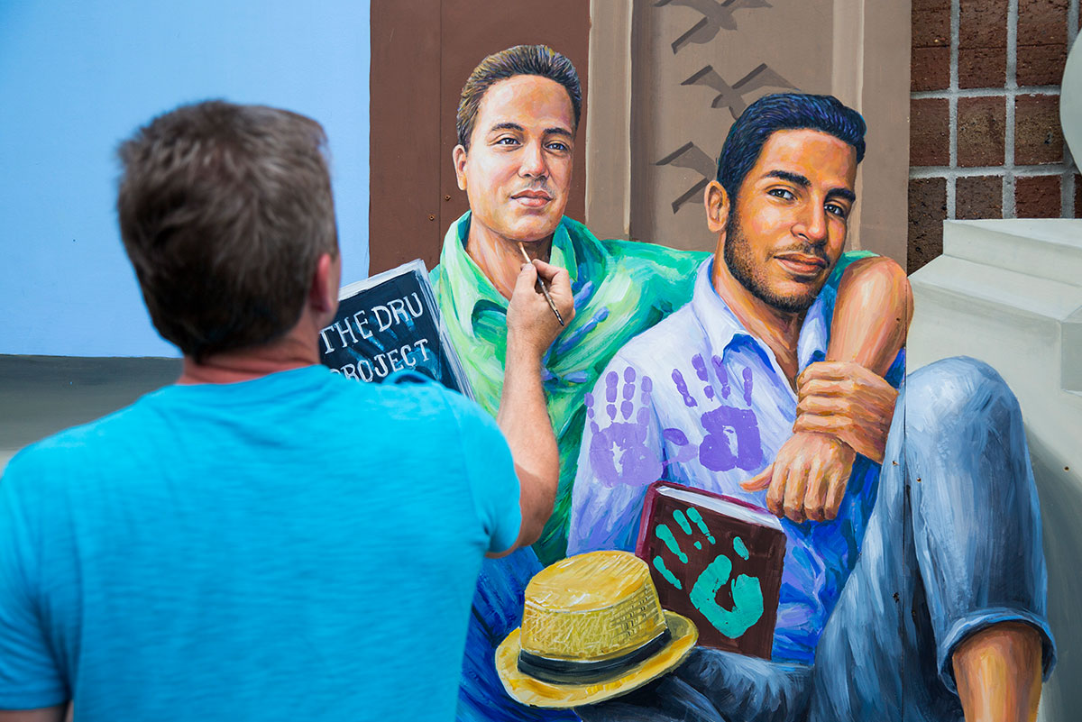 A man in a blue shirt is seen holding up a paintbrush to the chin of a painting of two men sitting together, one with his arm around the other.