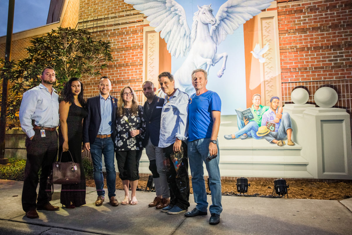 Five men and two women stand together facing the camera in front of the mural, which is lit up on a wall behind them. You can see a flying white horse rearing up and two men sitting on steps on the mural.