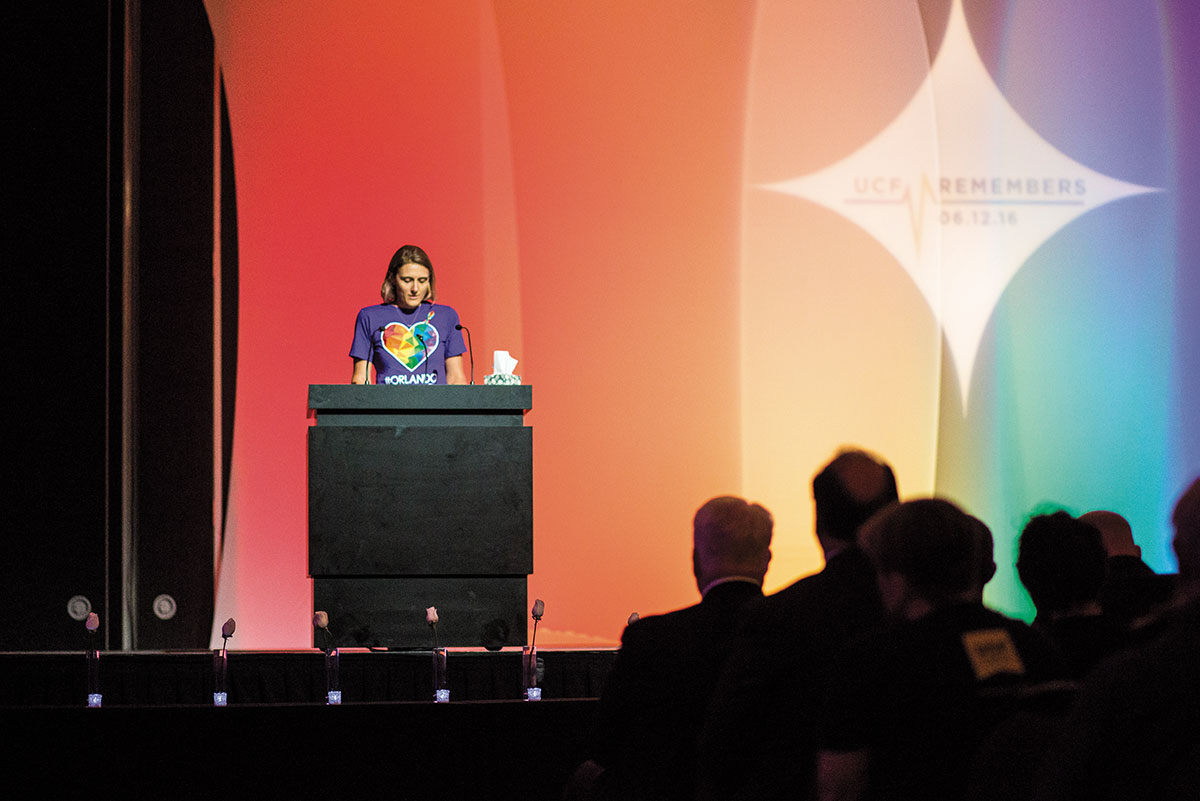A woman wearing a purple Orlando United shirt stands in front of a podium. Behind her is a screen with a giant rainbow.