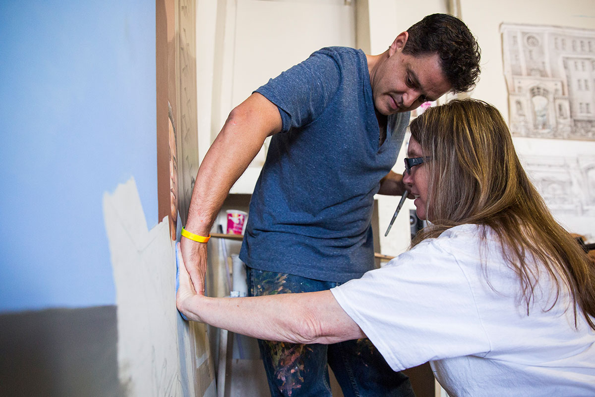 A woman in a white shirt holds her hand against a canvas while a man in a blue shirt puts his hand on top of hers, helping to soak the paint.