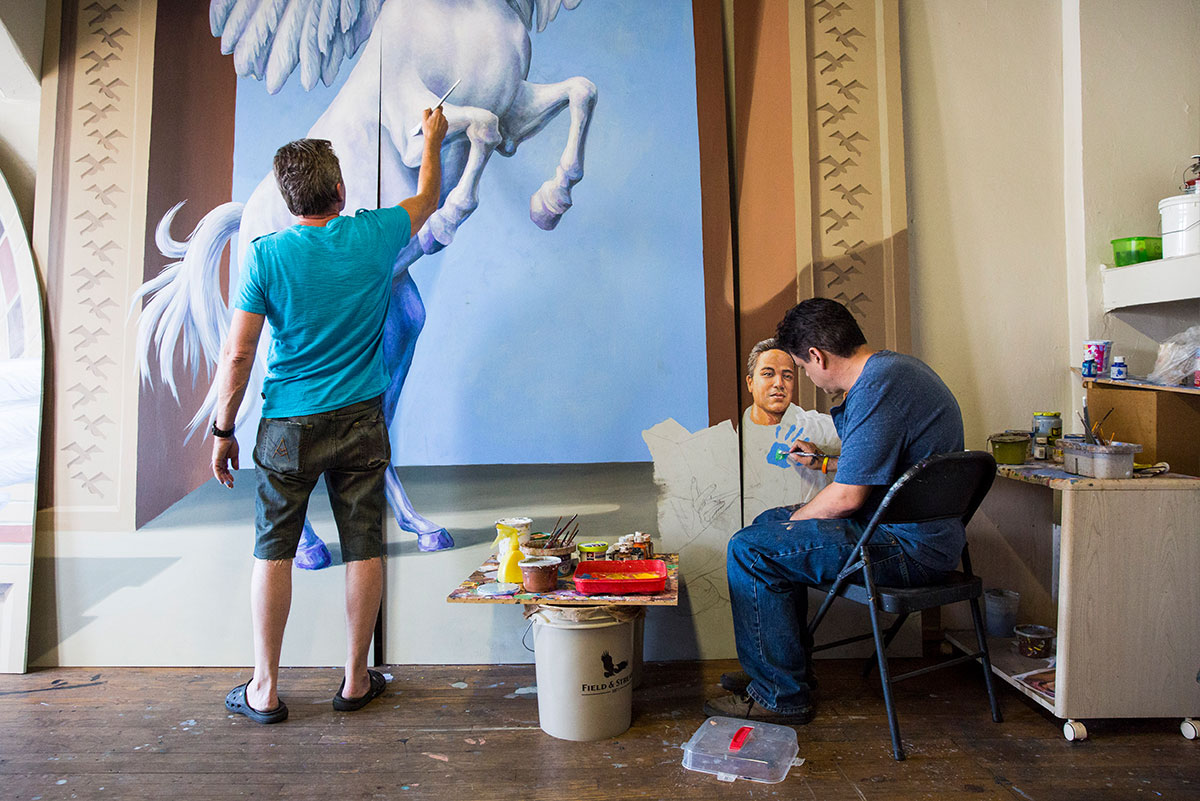 Yuriy Karabash, standing, and Michael Pilato, sitting, are painting part of a mural.