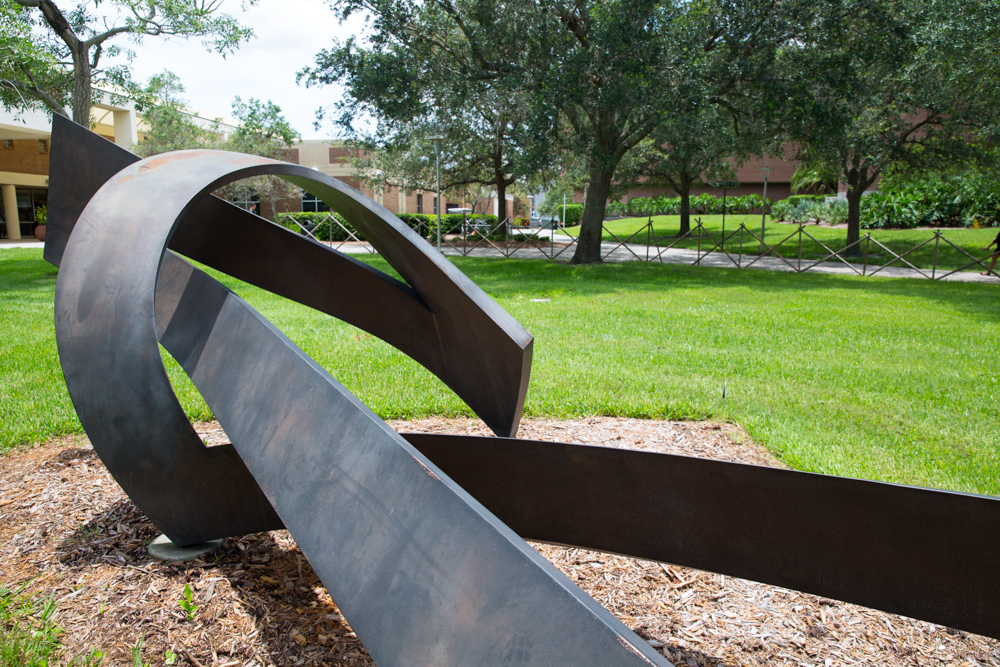 Public art makes its way onto the UCF campus either by an Art in State Buildings Program commission or through a generous donation — the latter of which is how the <em>Alamar</em> found its home on the grounds outside the Barnes and Nobles bookstore. The contemporary Corten steel sculpture is one of over 30 pieces loaned and eventually gifted to the university by George and Norma Kottemann, a couple who spent their life collecting and supporting the arts.