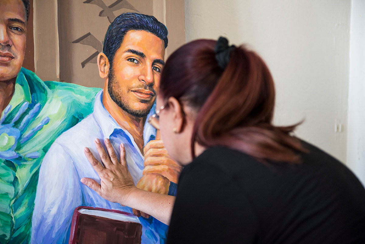 Mayra Guerrero presses her hand against a painting her son.