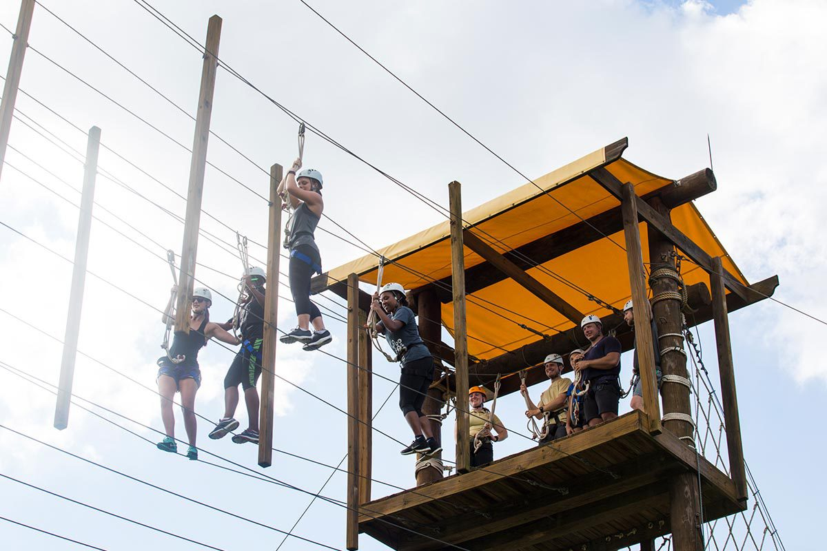 Four people wearing helmets try to cross wires suspended in the air.