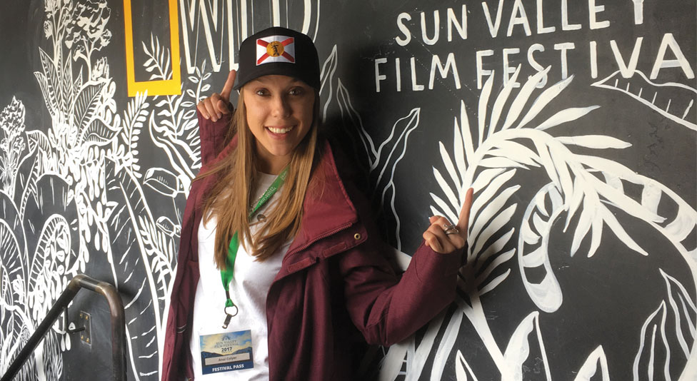Anai Coyler, wearing a black baseball cap with the Florida flag, stands in front of a chalkboard illustration, pointing to two logos: one for Nat Geo Wild and one for Sun Valley Film Festival