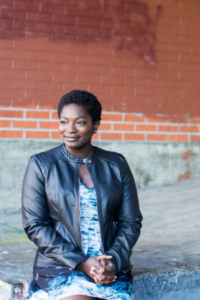 Melissa Amoi-Belinda Smith wearing a black leather jacket sits in front of a brick wall as she clasps her hands and looks off into the distance.