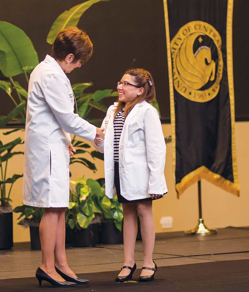Dean Deborah German presents Fernandez with her white coat. (Photo by Suht Wong)