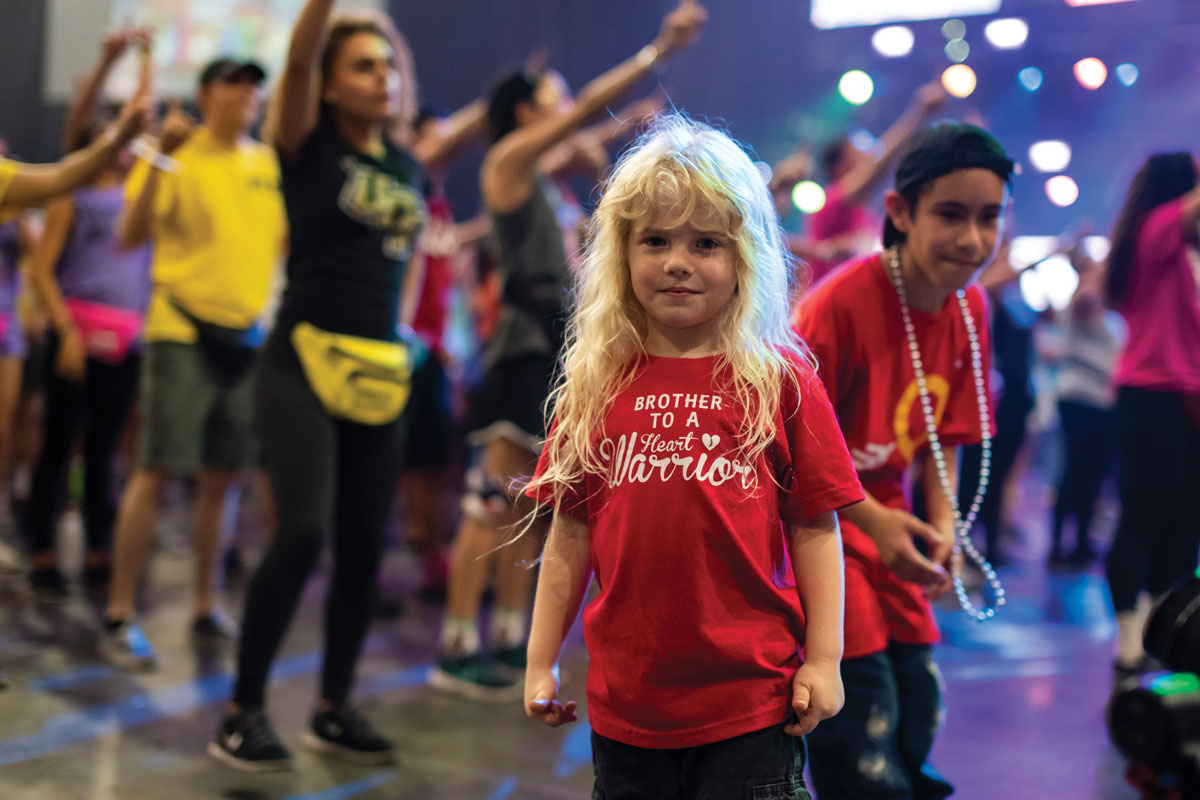 A young child with long blonde hair smiles at the camera as a crowd of people dance behind her.