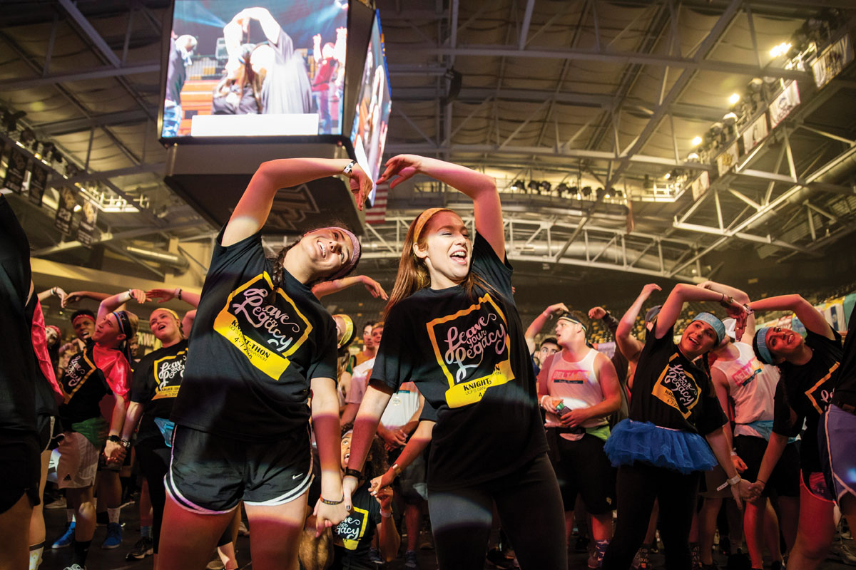 Two female students use their arms to form a heart while a crowd of people dance behind them in an arena.