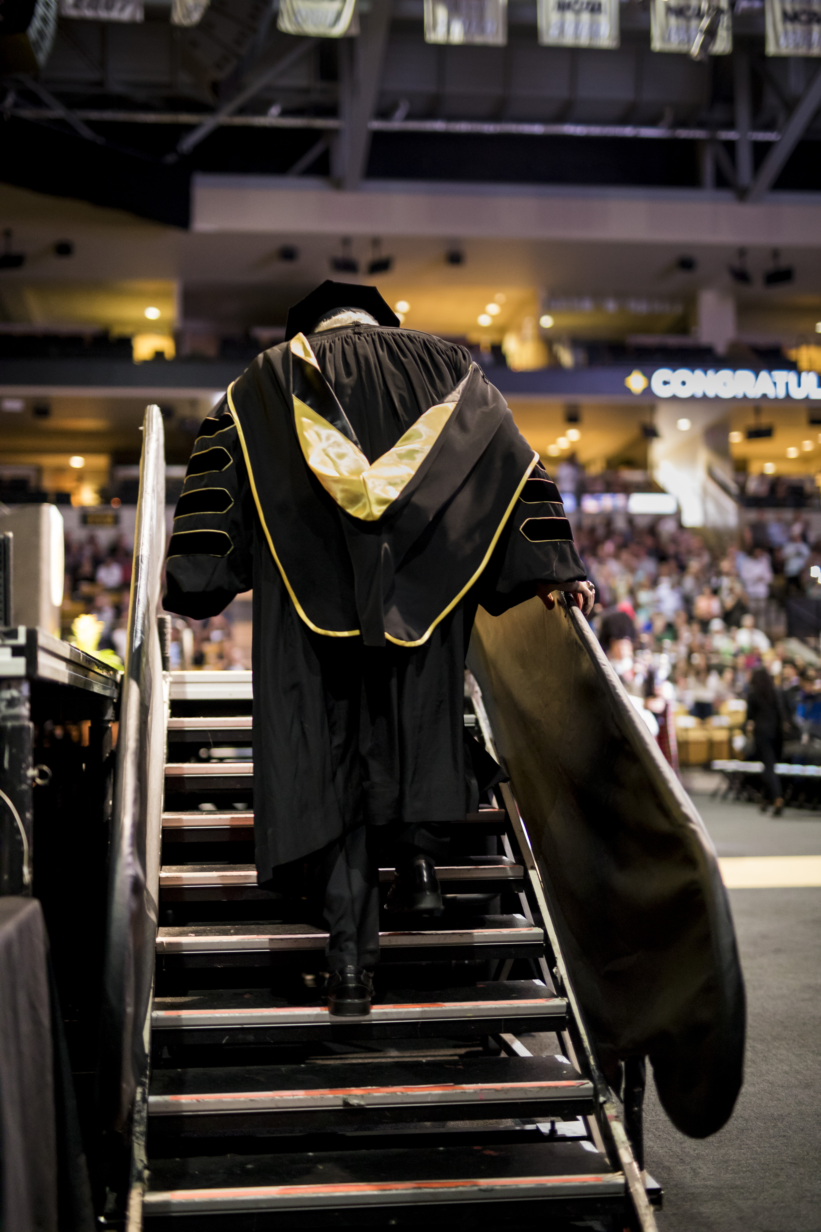 The back of John C. Hitt's gown displays black and gold as he walks up the steps to the CFE Arena stage.