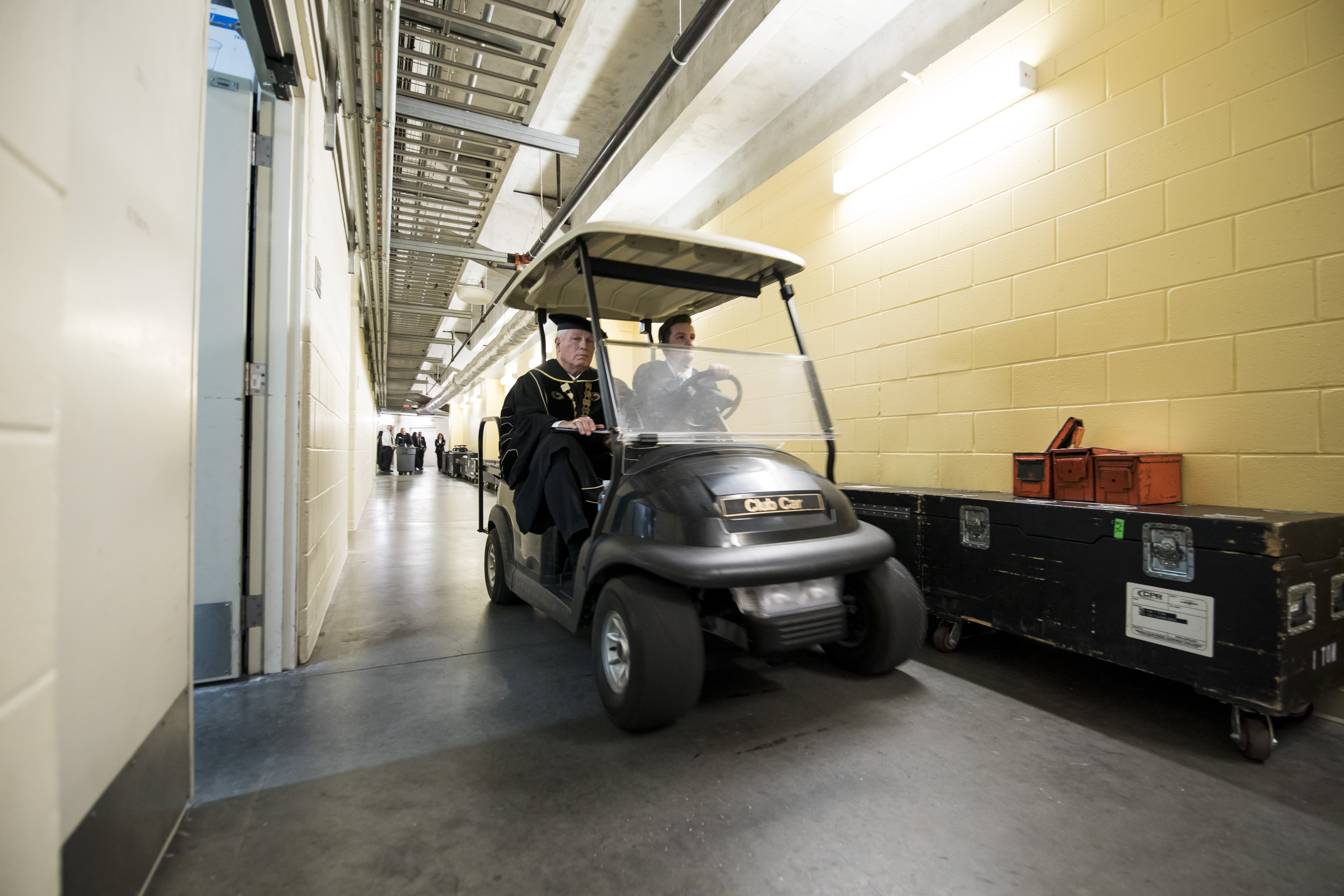 A man drives a golf cart through a hallway in CFE Arena as John C. Hitt wears a cap and gown and sits in the passenger seat .