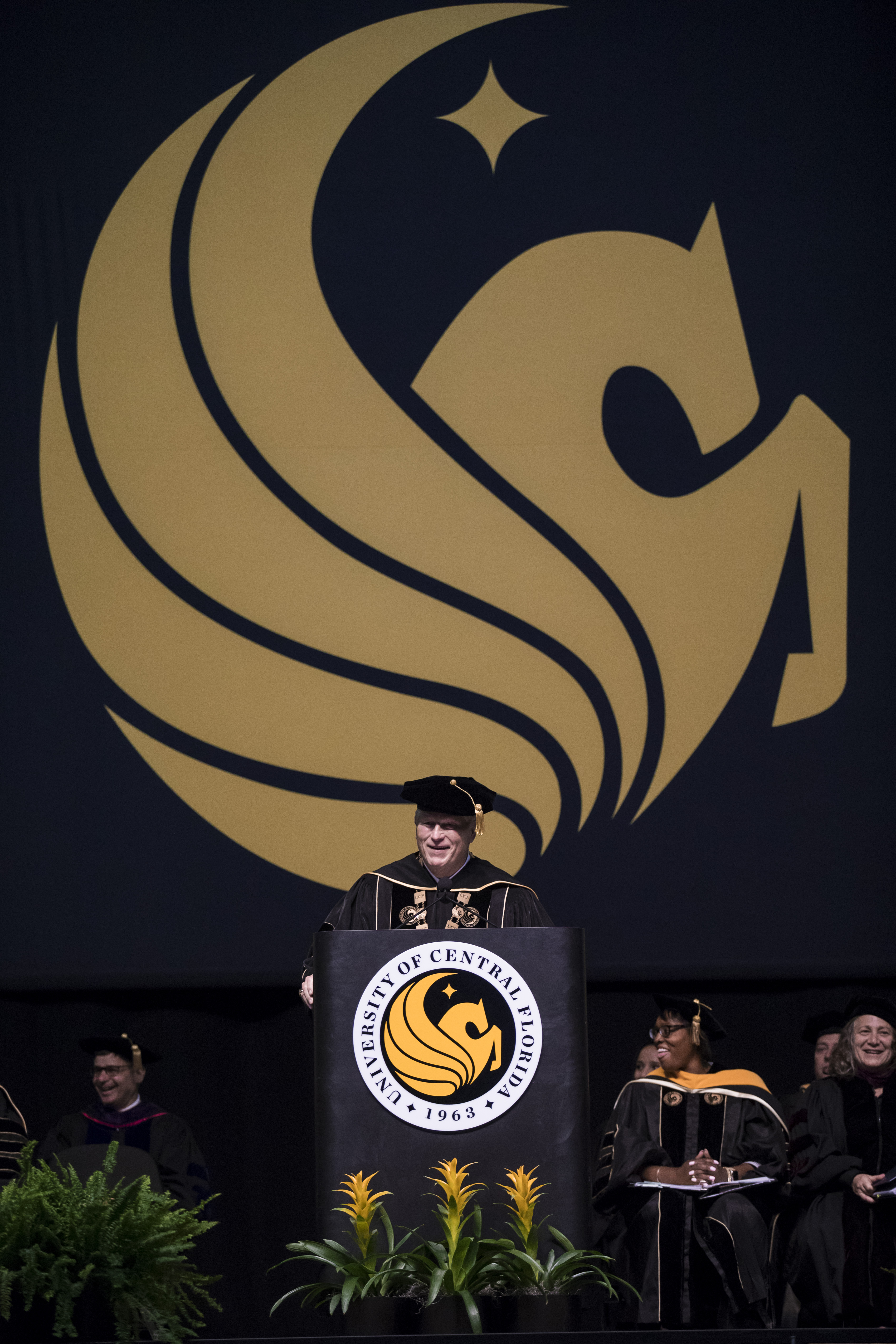 John C. Hitt speaks at a podium while wearing regalia as a yellow Pegasus symbol hangs behind him.