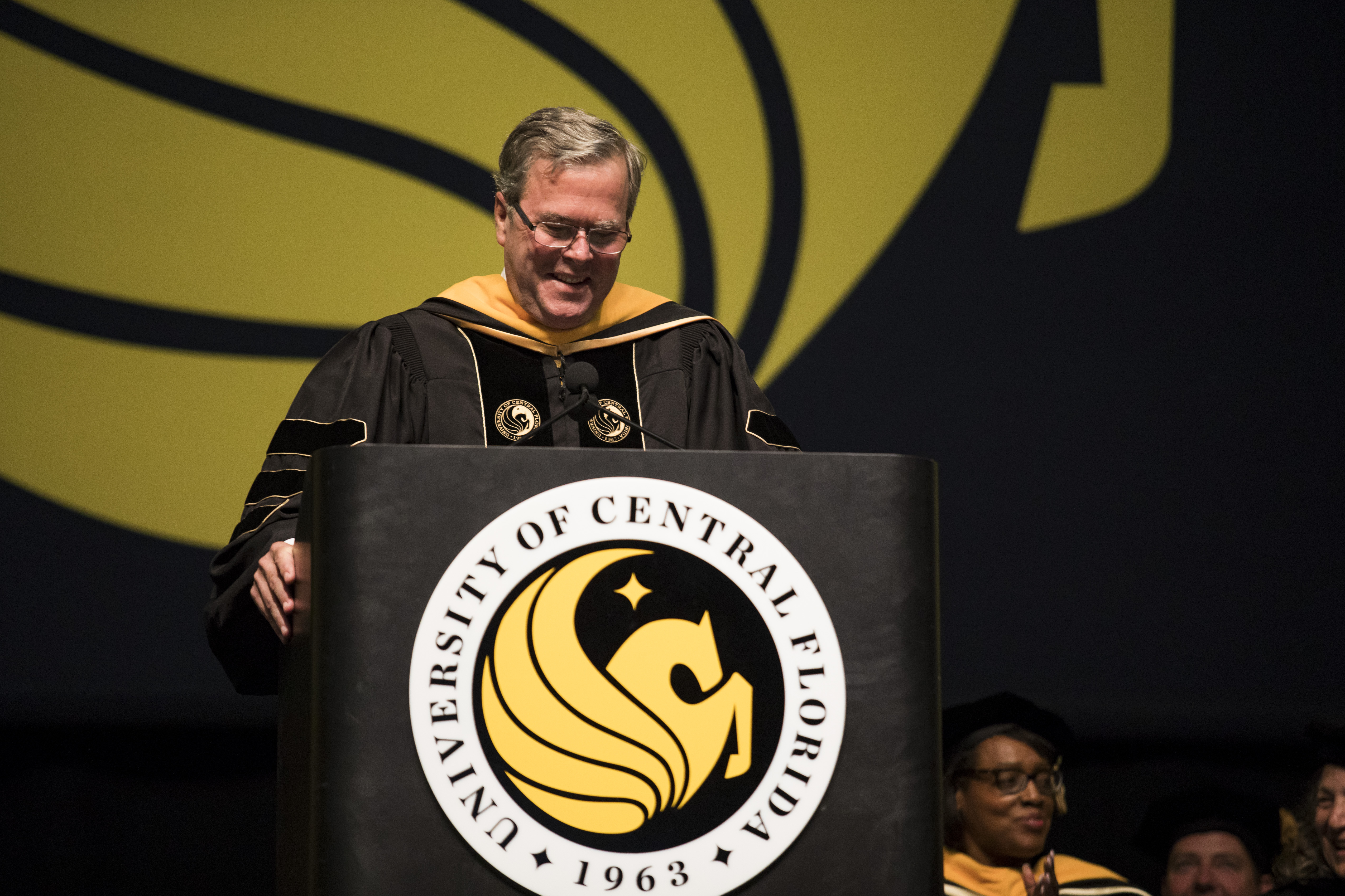 Former Florida Governor Jeb Bush wears a graduation gown as he stands behind a podium with the University of Central Florida Pegasus emblem on it.