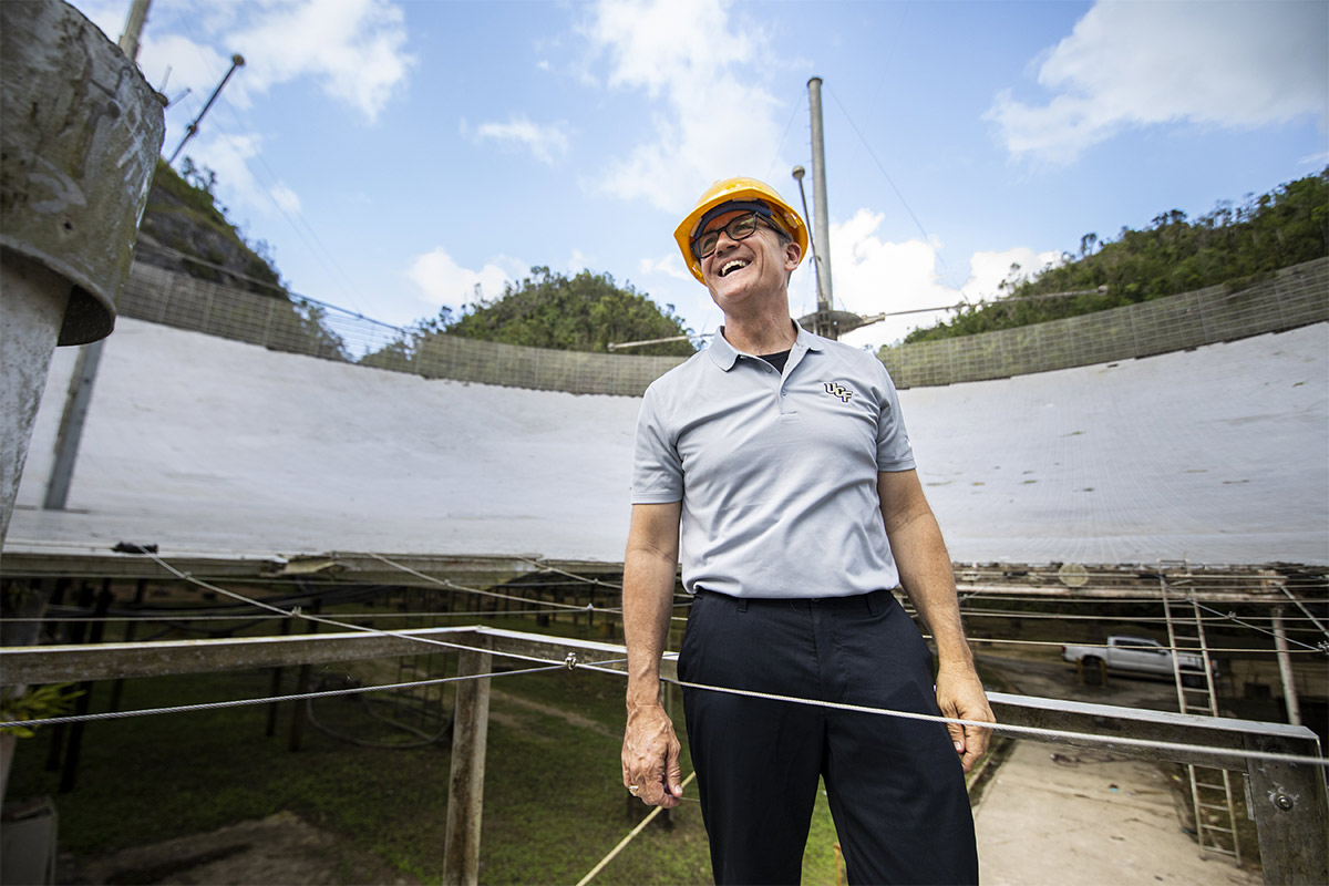 UCF President Dale Whittaker wearing yellow hard hat and glasses, grey polo, black pants, smiling near Arecibo.