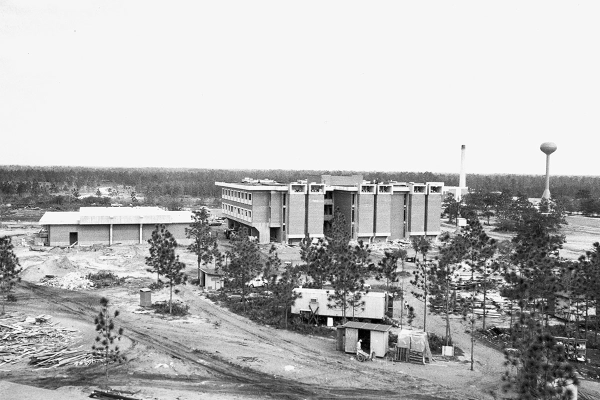 A black and white image shows a construction site with a finished building and trees.