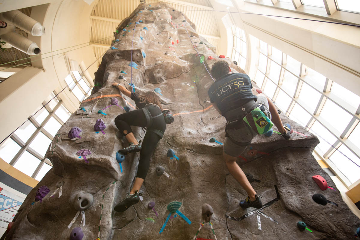 Two students climb a rock climbing wall.