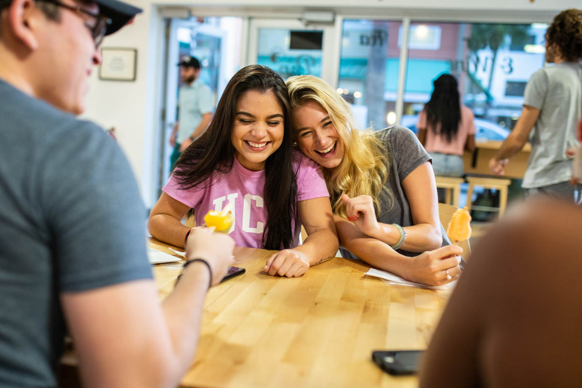 Two female students laugh and lean on each other while they sit at a table and eat popsicles.