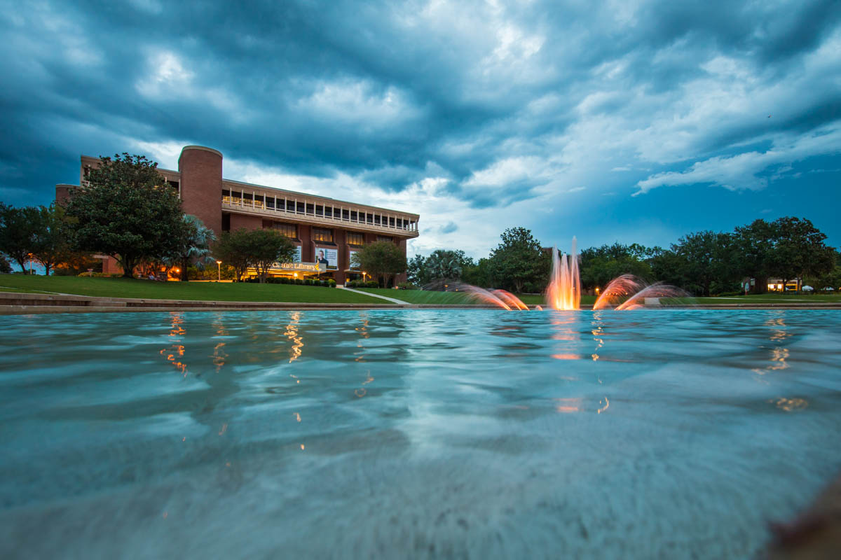 Lights brighten up the fountain of a pond in front of a library.