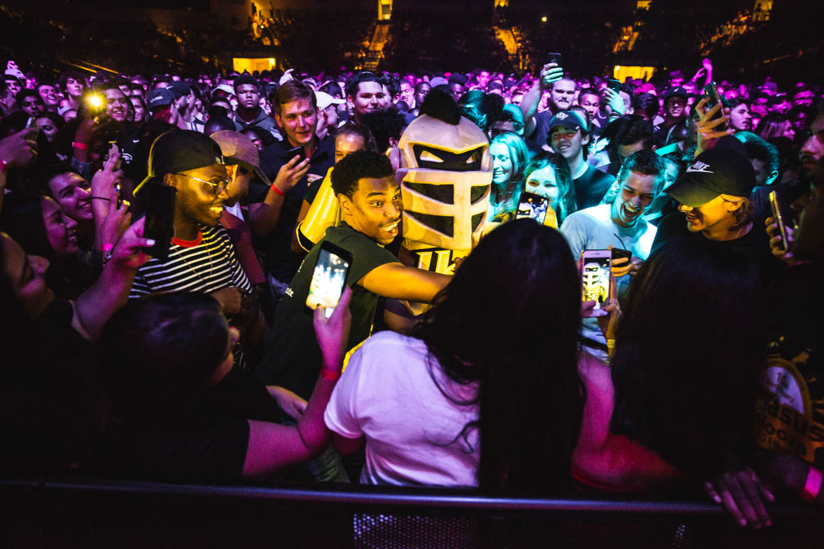 A guy hugs someone in a knight costume as a crowd forms around them.
