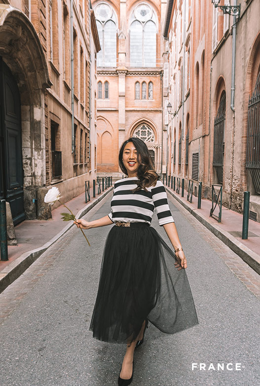 A woman in a black and white striped shirt and long black skirt holds a flower while walking down a bright alley.