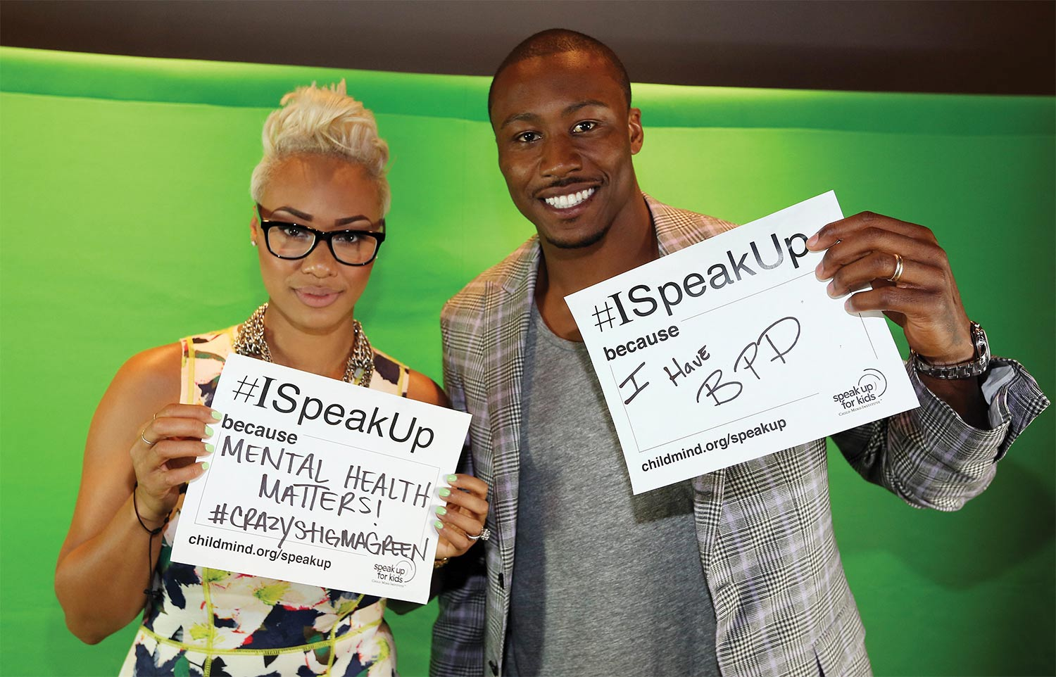 A man and a woman hold up signs against a green background.