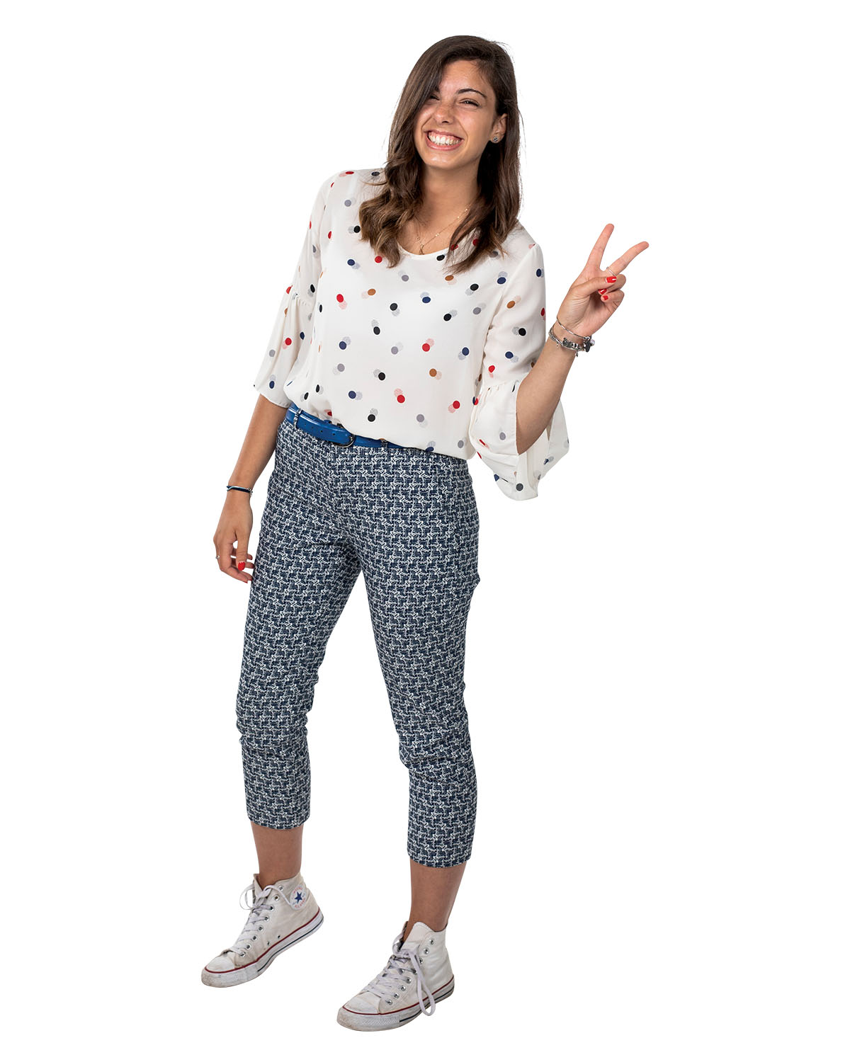 A woman in a white polka dot shirt and patterned pants holds up a peace sign with her fingers as she smiles.