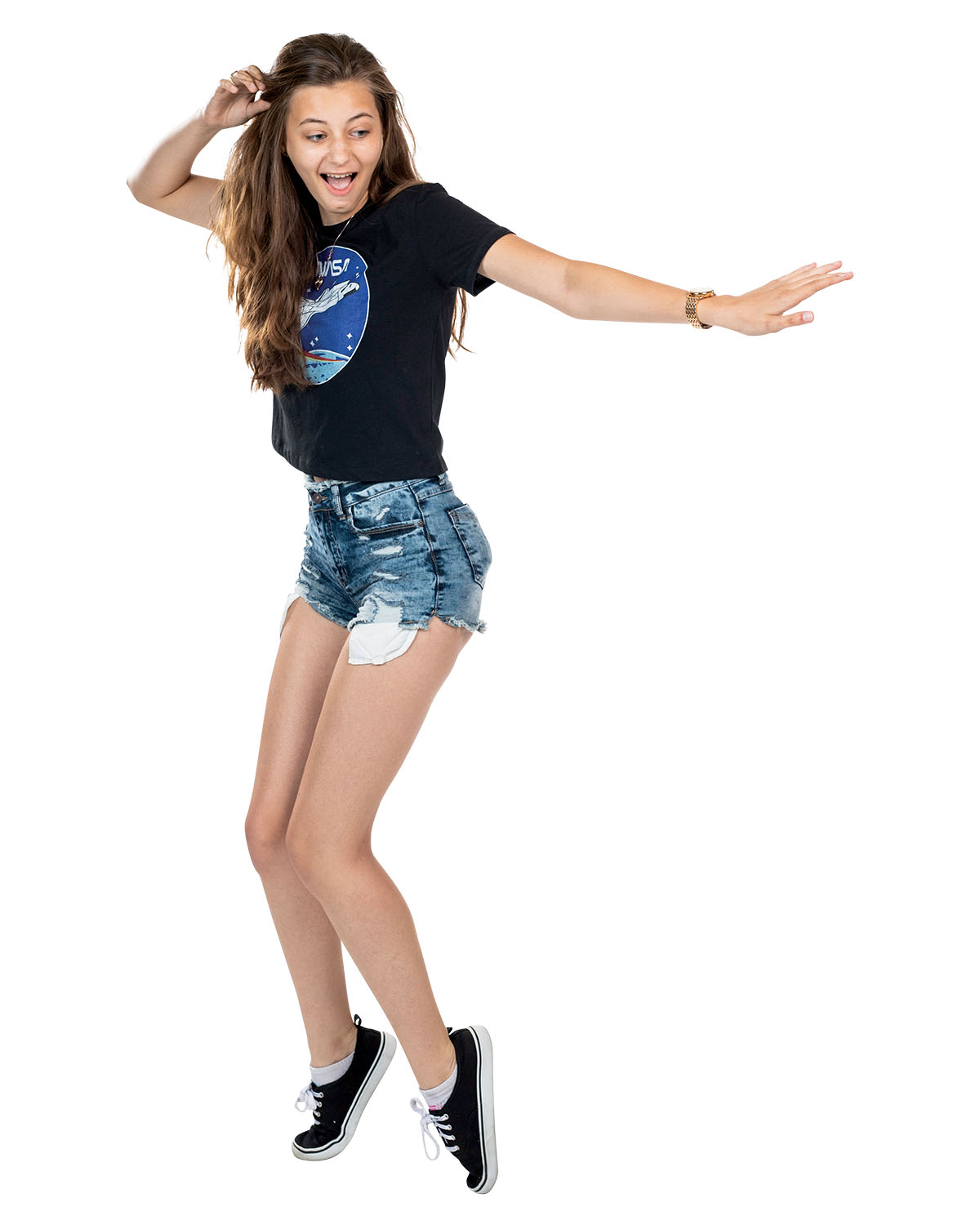 A woman in a black NASA T-shirt and ripped denim shorts stands on her tip-toes as she reaches an arm out and smiles.