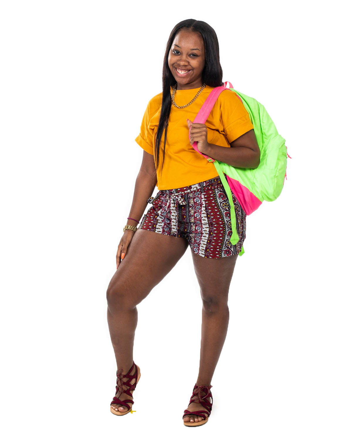 A woman in a yellow shirt and patterned shorts smiles as she wears a bright green backpack.