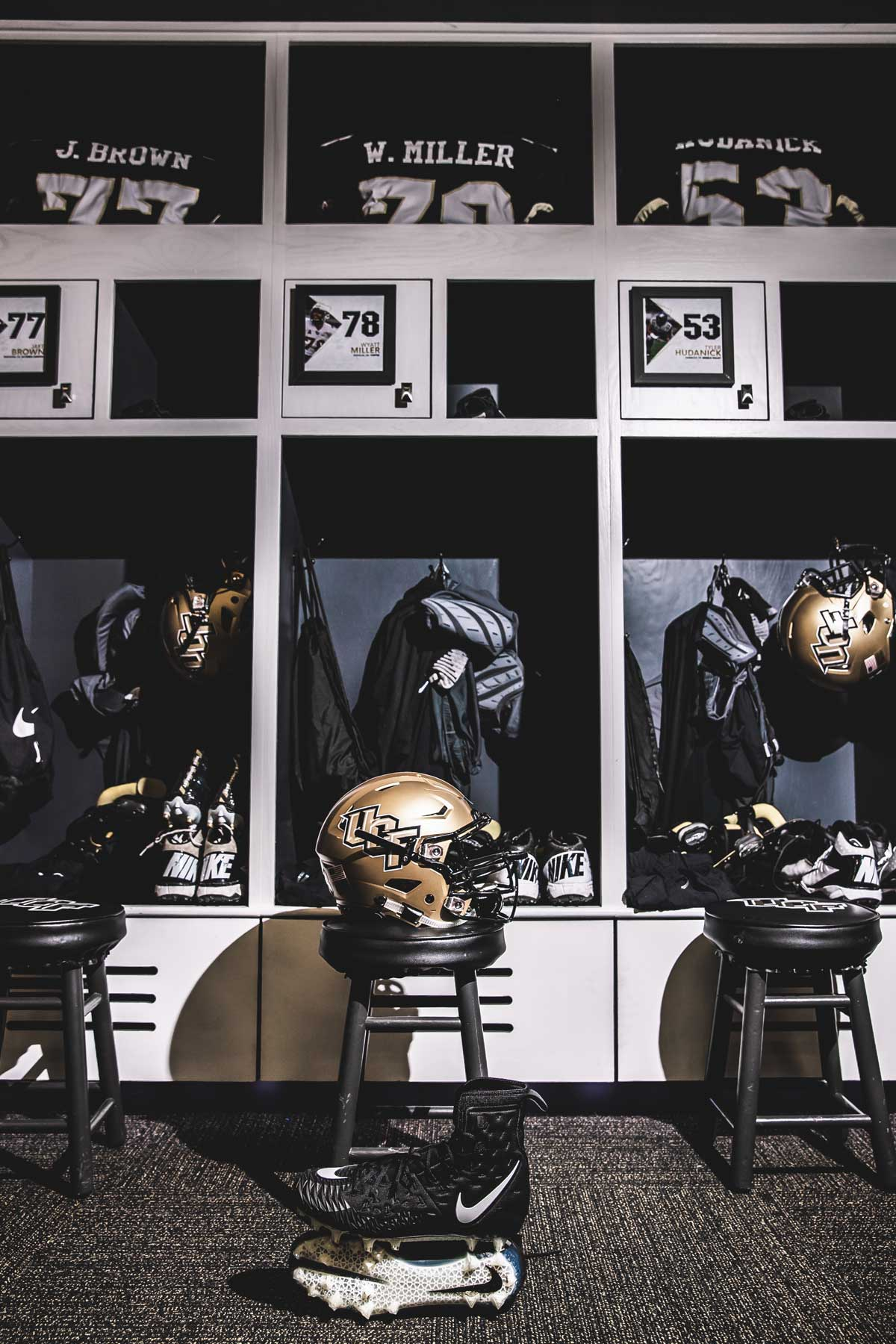 rows of lockers with a gold UCF helmet on a stool