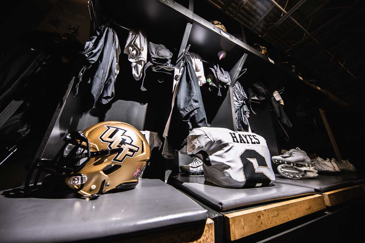 gold helmet and white #6 jersey in front of a row of lockers