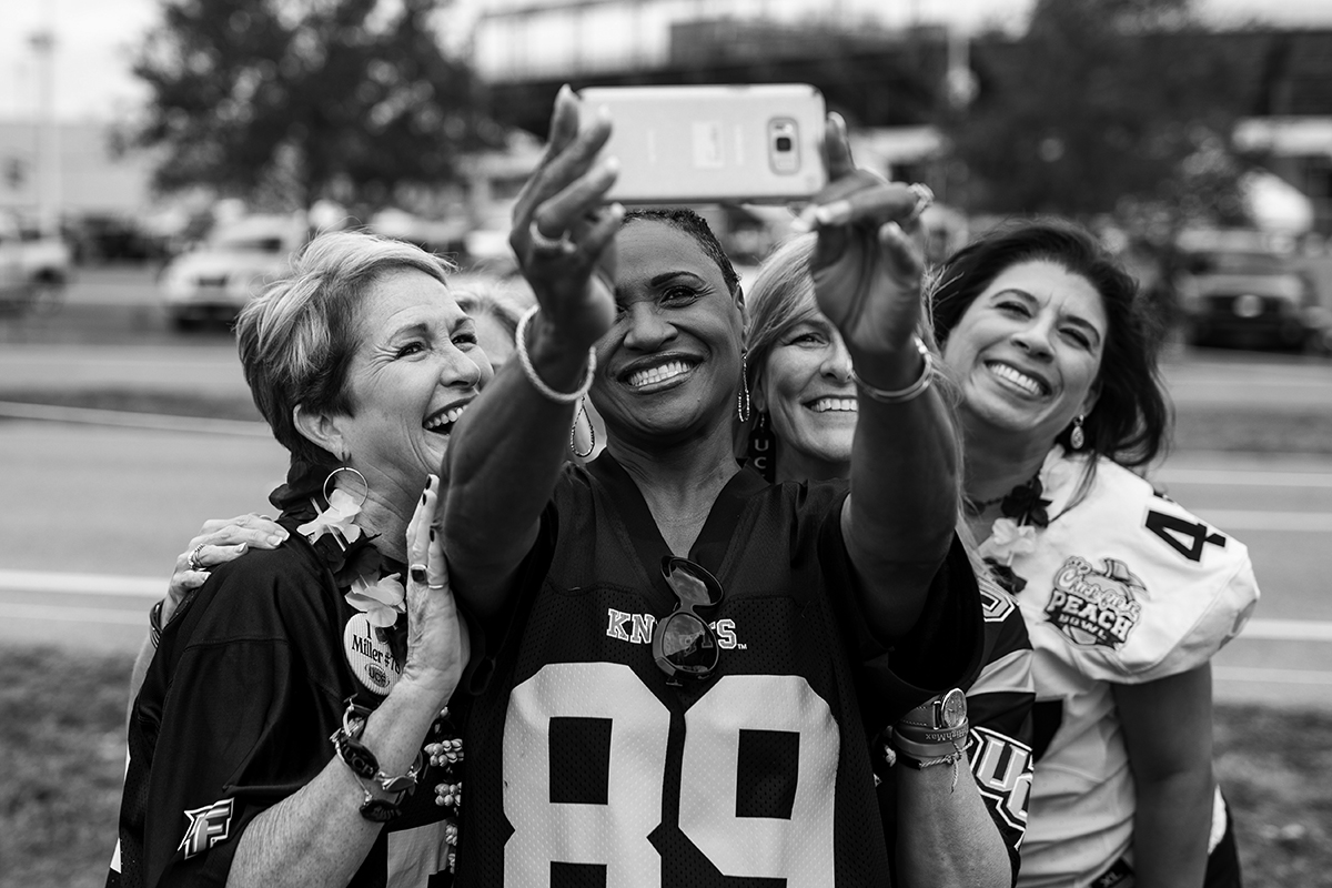 Group of ladies wearing UCF jerseys pose for selfie