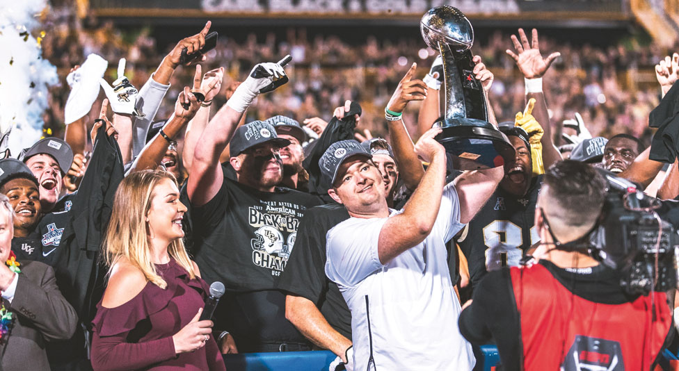 Josh Heupel, UCF football head coach holds up aac trophy with his team celebrating behind him