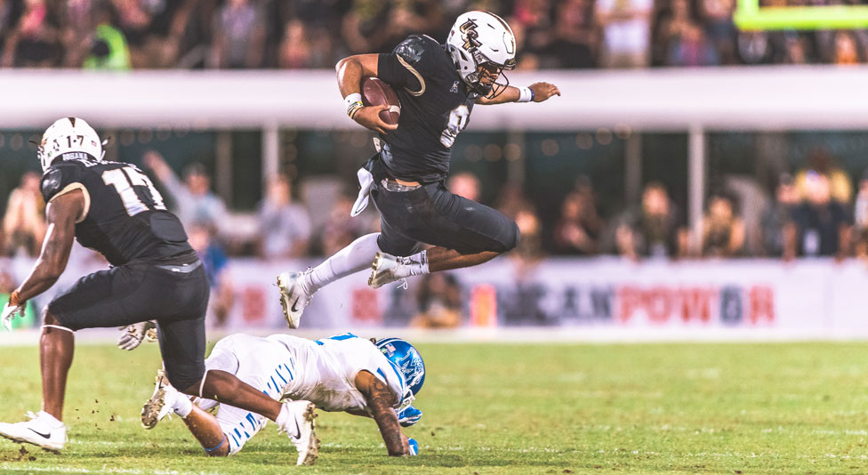 ucf quarterback Darriel Mack Jr. leaps over a memphis player